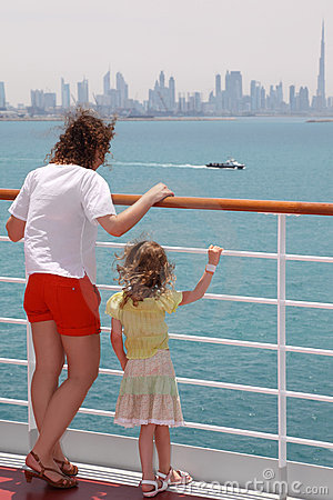 Mother and daughter standing on cruise liner deck