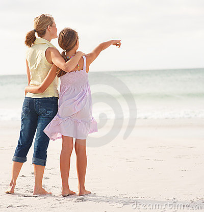 Mother and daughter standing together at beach