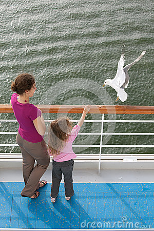 Mother daughter traveling boat feed seagulls