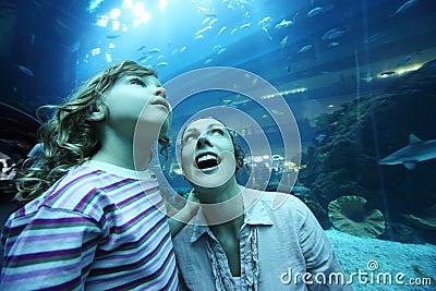 Mother and daughter in underwater aquarium tunnel