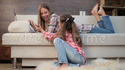 Mother and daughter using laptop and phone at home stock footage