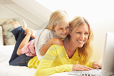 Mother And Daughter Using Laptop Relaxing On Sofa