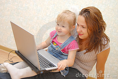 Mother and Daughter Using Laptop on wooden  floor