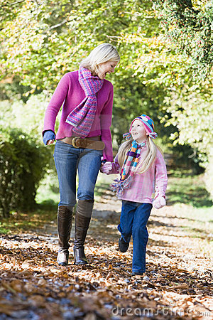 Mother and daughter walking along autumn path