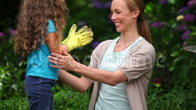 Mother and daughter wearing garden gloves. In a garden stock footage