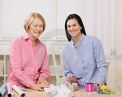 Mother and daughter wrapping gifts together