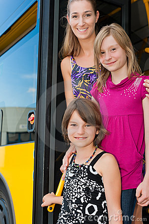 Mother and daughters looking out of a bus