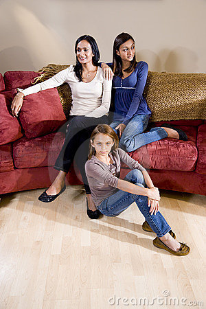 Mother and daughters sitting together at home in l