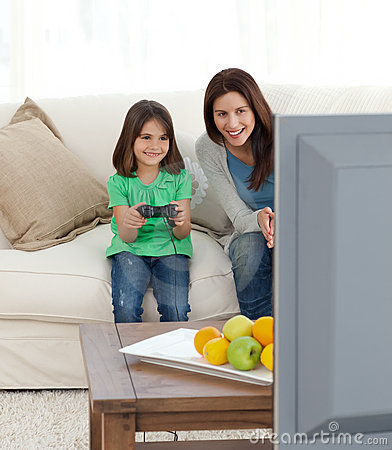 Mother encouraging her daughter playing video game
