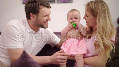 Mother and father with baby laughing. Portrait of happy family love child. Mother and father with baby laughing. Portrait of happy parents kissing baby on hands stock video