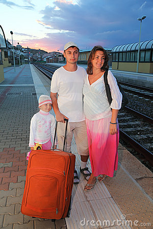 Mother, father and daughter with bag on platform