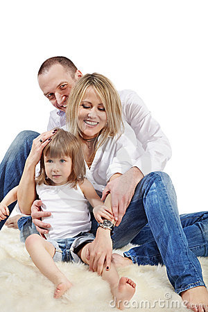 Mother, father and daughter sit on carpet Stock Photo