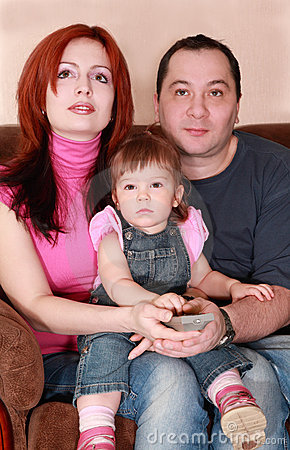 Mother, father and daughter sitting and watch TV