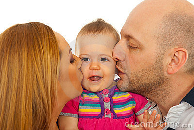Mother and father kissing baby