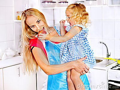 Mother  feed child at kitchen.