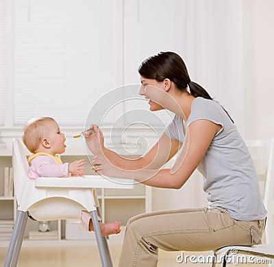 Mother feeding baby in highchair in kitchen