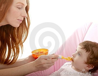 Mother feeding baby yellow spoon
