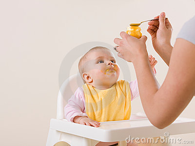 Mother feeding hungry baby in highchair