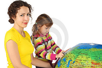 Mother and girl with stethoscope and big globe