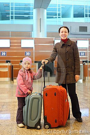 Mother and girl with suitcases standing at airport