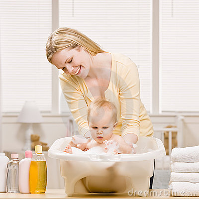 Mother give baby girl a bath