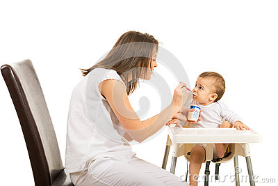 Mother gives her baby to eat yogurt