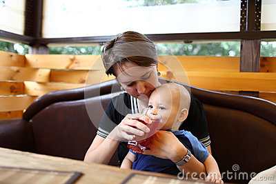 Mother gives to drink to son