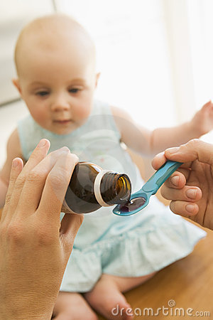 Mother giving baby medicine indoors