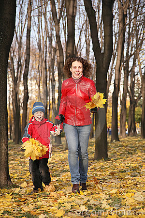 Mother goes for a walk with son. Autumn
