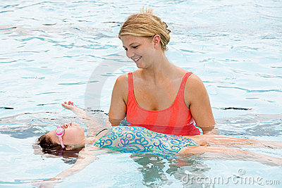 Mother Helping Daughter To Float on Her Back