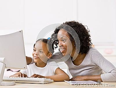 Mother helping girl do homework on computer