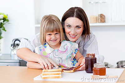 Mother helping her daughter prepare the breakfast