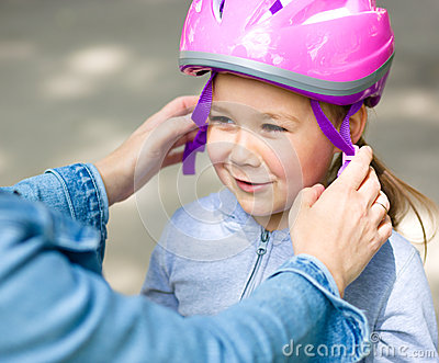 Mother is helping her daughter with safety helmet