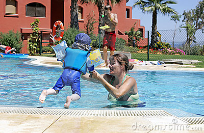 Mother helping her young son to swim and jump in a sunny swimmin
