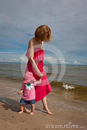Mother with her baby  having fun on the beach