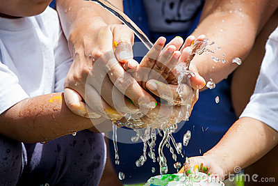 Mother and her child washing hands together after painted Stock Photo