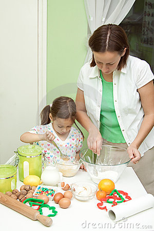 Mother and her daughter, bakeing in the kitchen