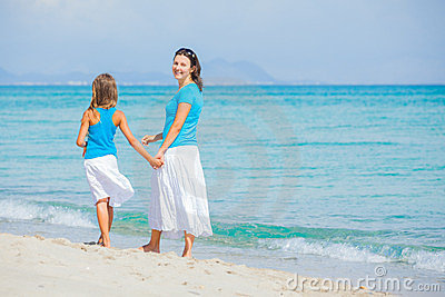Mother and her daughter having fun on beach