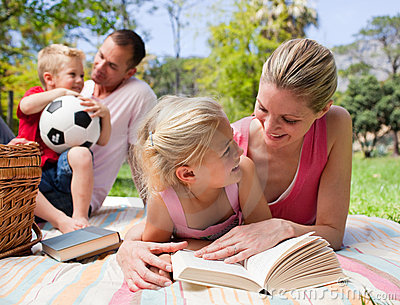 Mother and her daughter reading at a picnic