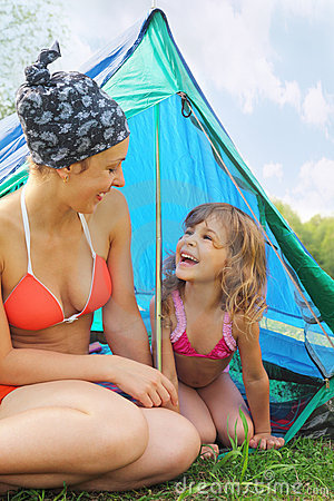 Mother and her daughter sitting near tent