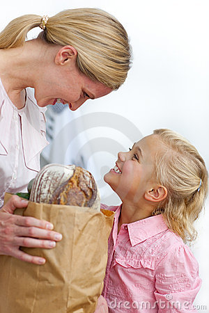 Mother and her daughter unpacking grocery bag