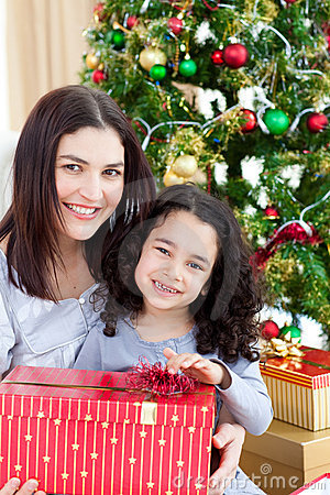 Mother and her girl opening Christmas gifts