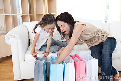 Mother and her girl opening shopping bags
