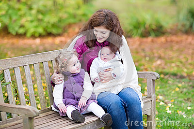 Mother with her kids on wooden bench in park