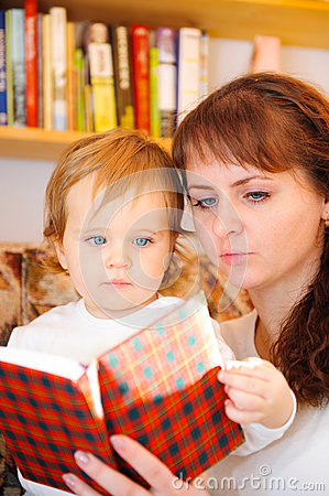 Mother with her little baby son reading book