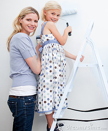 Mother and her little girl painting a room