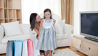 Mother and her little girl trying on dress
