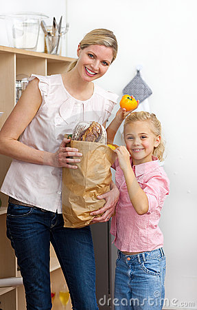 Mother and her Little girl unpacking grocery bag
