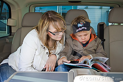 Mother and her son are reading a book