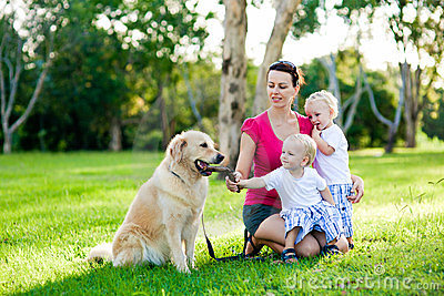 Mother and her two sons in the park with a dog